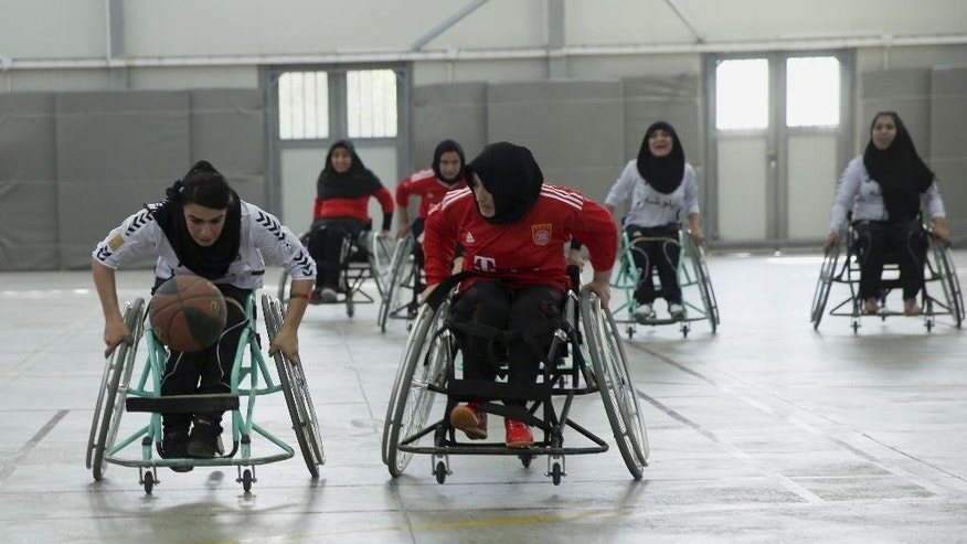 In this photo taken Tuesday, Oct. 28, 2014, a player from Balkh province (in withe) dribbles the ball as another from Herat province charges during Afghanistan's national wheelchair basketball tournament organized by the International Committee of the Red Cross (ICRC) in Kabul, Afghanistan. Many amputees in Afghanistan languish without access to care and become depressed and isolated. And with mines and unexploded ordinance still scattered across this country ravaged by decades of nonstop war, more will be maimed or lose limbs from explosions. However, an ICRC program offering sports to amputees has seen hundreds sign up to play wheelchair basketball. (AP Photo/Massoud Hossaini)