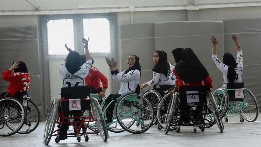 In this photo taken Tuesday, Oct. 28, 2014, players from Balkh province (in withe) celebrate during a match against the team from Herat province in Afghanistan's national wheelchair basketball tournament organized by the International Committee of the Red Cross (ICRC) in Kabul, Afghanistan. Many amputees in Afghanistan languish without access to care and become depressed and isolated. And with mines and unexploded ordinance still scattered across this country ravaged by decades of nonstop war, more will be maimed or lose limbs from explosions. However, an ICRC program offering sports to amputees has seen hundreds sign up to play wheelchair basketball. (AP Photo/Massoud Hossaini)