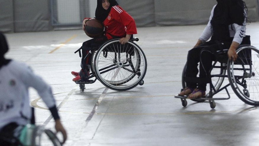 In this photo taken Tuesday, Oct. 28, 2014, a player from Herat province (in red) looks to pass the ball against a player from Balkh province during Afghanistan's national wheelchair basketball tournament organized by the International Committee of the Red Cross (ICRC) in Kabul, Afghanistan. Many amputees in Afghanistan languish without access to care and become depressed and isolated. And with mines and unexploded ordinance still scattered across this country ravaged by decades of nonstop war, more will be maimed or lose limbs from explosions. However, an ICRC program offering sports to amputees has seen hundreds sign up to play wheelchair basketball. (AP Photo/Massoud Hossaini)