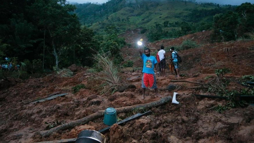 A man shines a torch as dusk falls at the site of a mudslide at the Koslanda tea plantation in Badulla district, about 220 kilometers (140 miles) east of Colombo, Wednesday, Oct. 29, 2014. The mudslide triggered by monsoon rains buried scores of workers' houses at the tea plantation, killing at least 10 people and leaving more than 250 missing, an official said. (AP Photo/Eranga Jayawardena)