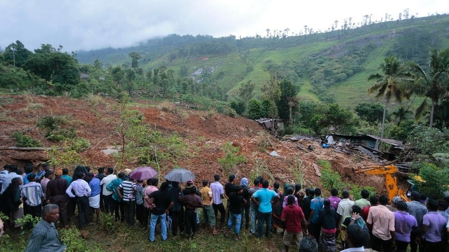 A crowd gathers to watch rescue operation at the site of a mudslide at the Koslanda tea plantation in Badulla district, about 220 kilometers (140 miles) east of Colombo, Wednesday, Oct. 29, 2014. The mudslide triggered by monsoon rains buried scores of workers' houses at the tea plantation, killing at least 10 people and leaving more than 250 missing, an official said. (AP Photo/Eranga Jayawardena)