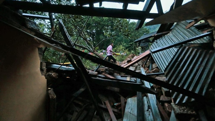 Sri Lankans walk past a damaged house at the site of a mudslide at the Koslanda tea plantation in Badulla district, about 220 kilometers (140 miles) east of Colombo, Wednesday, Oct. 29, 2014. The mudslide triggered by monsoon rains buried scores of workers' houses at the tea plantation, killing at least 10 people and leaving more than 250 missing, an official said. (AP Photo/Eranga Jayawardena)
