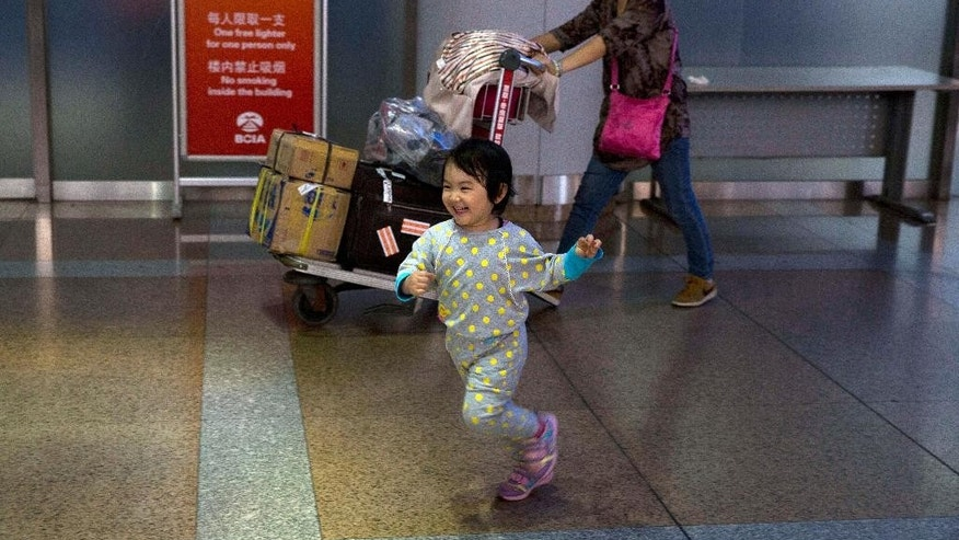 A child runs towards a family member receiving her at the arrival hall of the international airport in Beijing, China, Thursday, Oct. 30, 2014. Levels of self-reported well-being in fast-growing nations like Indonesia, China and Malaysia now rival those in US, Germany and the United Kingdom, rich nations which have long topped the happiness charts, according to a Pew Research Center global survey released Friday that it showed how national income was closely linked to personal life satisfaction. (AP Photo/Ng Han Guan)