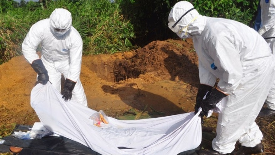 Oct. 27, 2014: Health workers prepare to place the body of a man who was suspected of dying from the Ebola virus into a grave on the outskirts of Monrovia, Liberia.