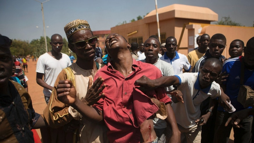 October 30, 2014 - An anti-government protester is shot in Ouagadougou, capital of Burkina Faso. Thousands of protesters marched on Burkina Faso's presidential palace after burning the parliament building and ransacking state television offices Thursday, forcing President Blaise Compaore to scrap a plan to extend his 27-year rule. Emergency services said at least three protesters were shot dead and several others wounded by security forces.