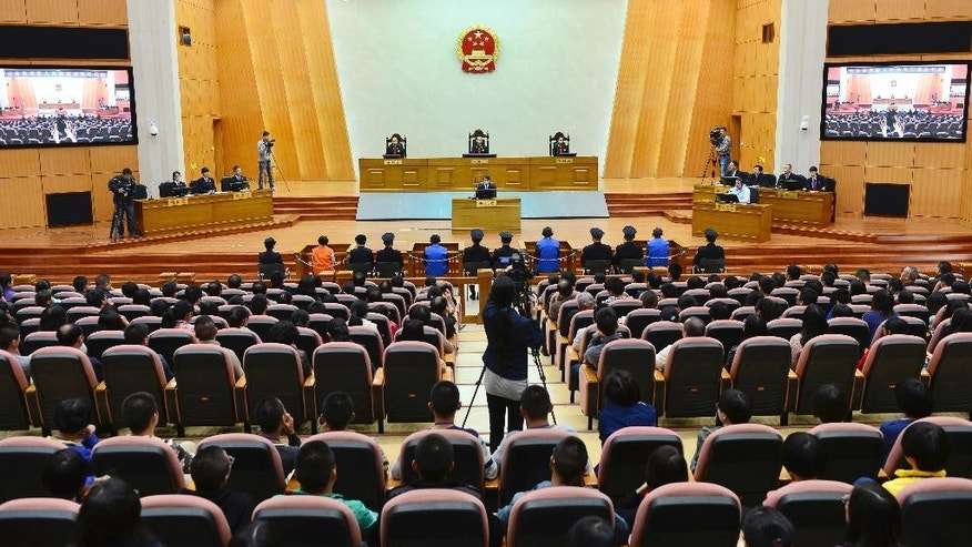 """In this photo released by China's Xinhua news agency, three defendants, in blue, sit during their trial at the Higher People's Court of Yunnan Province in Kunming, capital of southwest China's Yunnan Province, Friday, Oct. 31, 2014. The court upheld the death sentences of the three men convicted of organizing the brutal knife attack that killed 31 people earlier this year outside a railway station in the southern city of Kunming. The court rejected appeals and upheld sentences handed out last month by a lower court, saying that the three men """"all played a role in organizing, leading and plotting the terrorist activities at the Kunming Railway Station."""" (AP Photo/Xinhua, Liu Xuebin) NO SALES"""