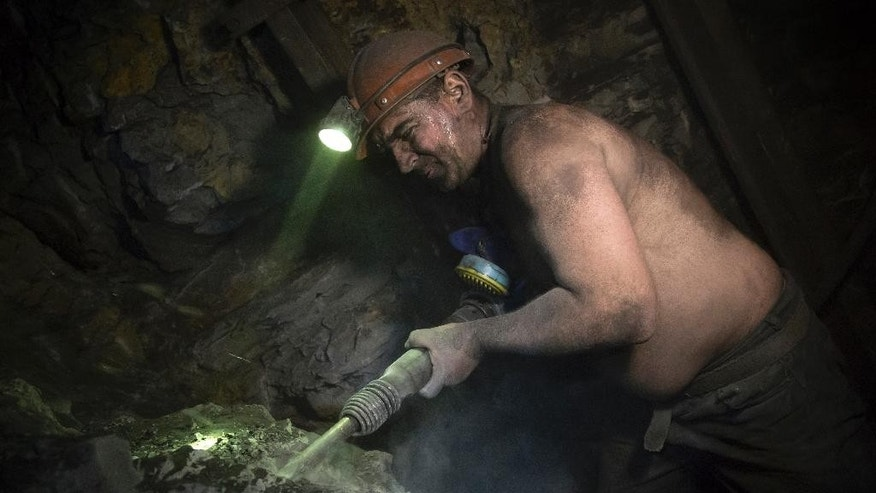 In this photo taken Thursday, Oct. 30, 2014, miner Vitaly Khristich uses a jackhammer at the Chelyuskintsev coal mine in the city of Donetsk, eastern Ukraine. Khristich is one of hundreds of miners who each day brave the artillery fire that flares between pro-Russian separatist rebels and Ukrainian troops and go down - deep, deep down - into the local mines. (AP Photo/Dmitry Lovetsky)