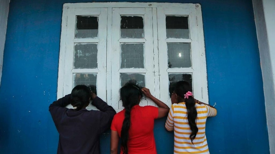 Three Sri Lankan mudslide survivors peep through a window to watch government officials interviewing other survivors to gather information on their missing relatives inside a relief center in Punagala in Badulla district