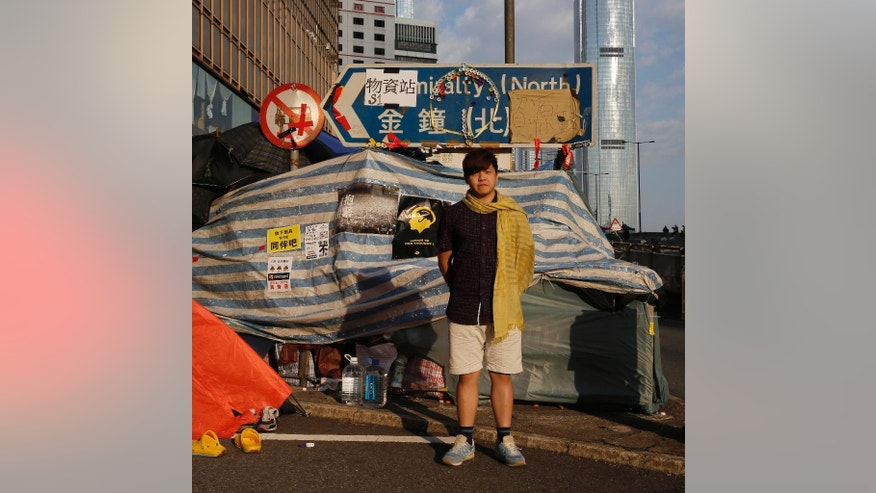 """In this Friday, Oct. 10, 2014 photo, Kelvin Lee, 21, a student studying aviation management, poses for a portrait in front of a makeshift tent on a main road in an occupied area near government headquarters in Hong Kong. """"It has made many students begin to show political awareness. Me as an example, I've always been nonchalant toward politics. But since the happening of this movement, I've started to pay more attention to it. Honestly, in the imminent short term, Hong Kong will not have too many changes. But in the long run, this movement is an important milestone."""" (AP Photo/Vincent Yu)"""