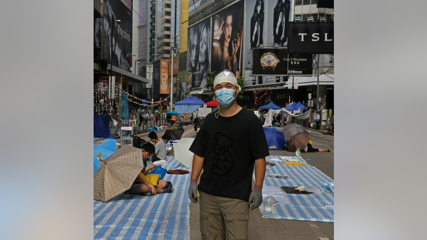 """In this Friday, Oct. 10, 2014 photo, Melvin Lee, 42, an engineer, poses for a portrait on a main road in the occupied areas at Causeway Bay district in Hong Kong. Lee said """"We have never been this resolute, never this determined. When Hong Kongers want to do something, no outside force can change it. This movement is reshuffling Hong Kong. Hong Kongers will be more concerned with issues on rights, and be more careful on its political policy. They will not simply allow others to represent them ... but instead will express their views by themselves."""" (AP Photo/Vincent Yu)"""
