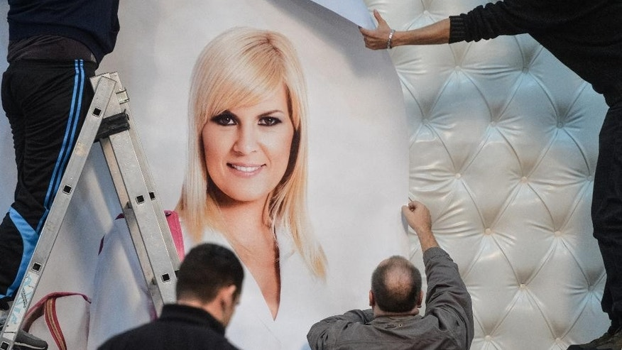 FILE - In this October 23, 2014, file picture A crew of workers install a campaign poster depicting Elena Udrea leader of the Popular Movement Party, in Bucharest, Romania. Romanians go to the polls on Sunday to elect a new leader as President Traian Basescu steps down after 10 years. Former tourism minister Elena Udrea is well-known for her close relationship with the outgoing president and for her glitzy wardrobe _ once sparking outrage by wearing a Dolce & Gabbana dress that cost as much as many Romanians earn in a month (AP Photo/Andreea Alexandru, Mediafax) ROMANIA OUT