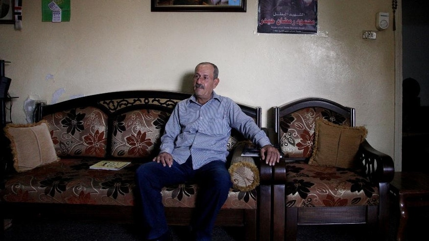 In this Tuesday, Oct. 28, 2014 photo, Ramadan Haidar, father of Mahmoud, a 23-year-old Syrian who was killed while fighting in the military, sits in his living room under photos of his son, in the city of Tartous, the capital of a coastal province in Syria. More soldiers have been killed from Tartous than any other region in Syria, in the fighting to quell an armed rebellion seeking to topple Bashar Assad's rule, now in its fourth year. (AP Photo/Diaa Hadid)