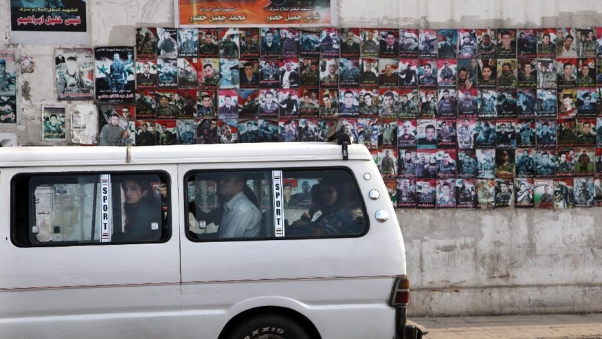 In this Tuesday, Oct. 28, 2014 photo, a mini bus stops in front of posters of slain Syrian soldiers pasted on a wall on a main street in the city of Tartous, the capital of a coastal province in Syria. More soldiers have been killed from Tartous than any other region in Syria, in the fighting to quell an armed rebellion seeking to topple Bashar Assad's rule, now in its fourth year. (AP Photo/Diaa Hadid)