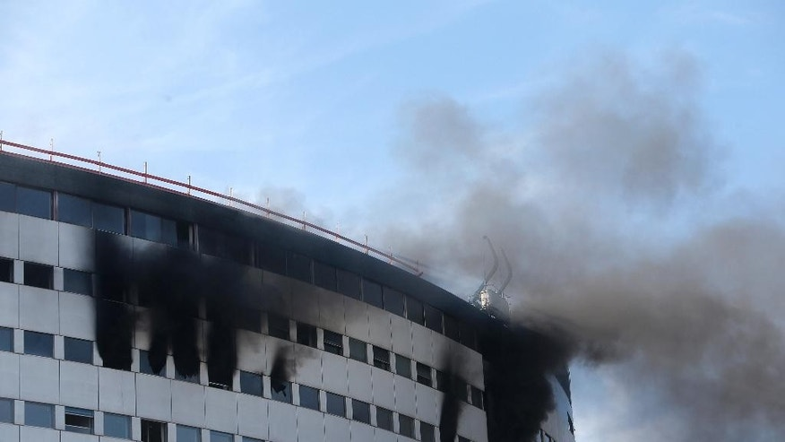 Black smoke are pouring from windows of the state radio headquarters, known as Maison de la Radio, in Paris, France, Friday, Oct.31, 2014. The massive building was undergoing renovations when the fire began. (AP Photo/Thibault Camus)