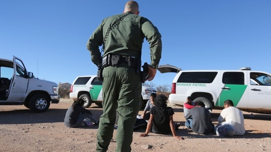 WALKER CANYON, AZ - MARCH 06:  A U.S. Border Patrol agent guards a group of Mexican immigrants caught after they crossed into the United States on March 6, 2013 near Walker Canyon, Arizona. Due to broad federal sequestration budget cuts, Border Patrol agents are expected to begin taking unpaid furlough days in April, as Customs and Border Protection funding is expected to be reduced by more than $500 million. (Photo by John Moore/Getty Images)