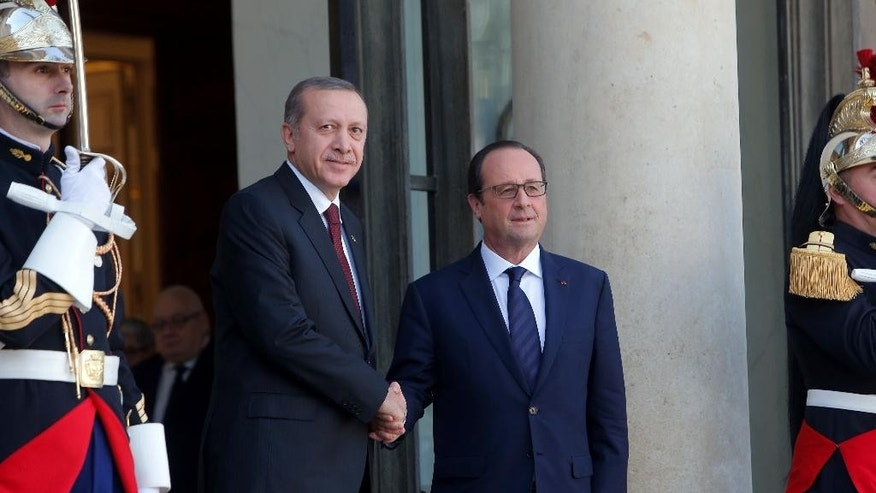 French President Francois Hollande, right, shakes hands with Turkish President Recep Tayyip Erdogan before their talks at the Elysee Palace in Paris, Friday, Oct.31, 2014. A vanguard force of Iraqi peshmerga troops entered the embattled Syrian border town of Kobani from Turkey on Thursday, part of a larger group of 150 fighters that the Kurds hope will turn back an offensive by militants of the Islamic State group. (AP Photo/Thibault Camus)