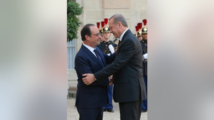 French President Francois Hollande, left, welcomes Turkish President Recep Tayyip Erdogan at the Elysee Palace in Paris, Friday, Oct.31, 2014. A vanguard force of Iraqi peshmerga troops entered the embattled Syrian border town of Kobani from Turkey on Thursday, part of a larger group of 150 fighters that the Kurds hope will turn back an offensive by militants of the Islamic State group. (AP Photo/Thibault Camus)