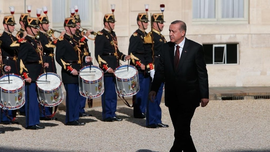 Turkish President Recep Tayyip Erdogan walks past Republican Guards before talks with French President Francois Hollande at the Elysee Palace in Paris, Friday, Oct.31, 2014. A vanguard force of Iraqi peshmerga troops entered the embattled Syrian border town of Kobani from Turkey on Thursday, part of a larger group of 150 fighters that the Kurds hope will turn back an offensive by militants of the Islamic State group. (AP Photo/Thibault Camus)