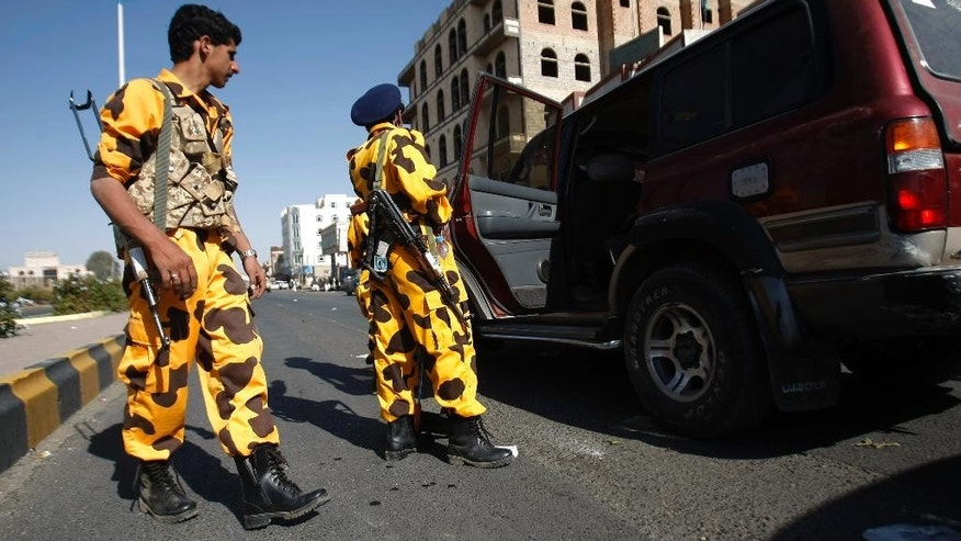Houthi Shiite Yemenis wearing police uniforms check a vehicle at a street ahead of a tribal meeting held by Houthi Shiite rebels in Sanaa, Yemen, Friday, Oct. 31, 2014. Yemen's Shiite rebels, who are in control of the capital, gave President Abed Rabbo Mansour Hadi 10 days starting Friday to form a government, hinting at a takeover attempt if their demands are not met. (AP Photo/Hani Mohammed)