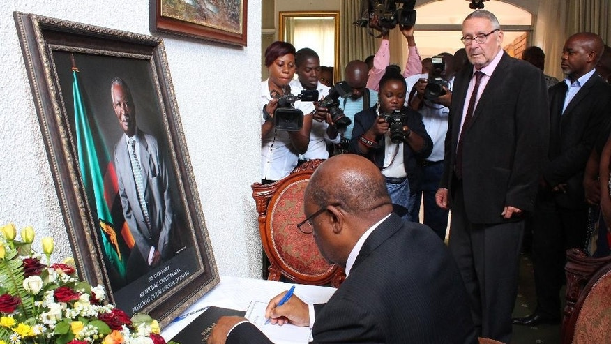 Acting Zambian president Guy Scott, second from right, watches over as eductaion minister John Phiri, foreground, signs a book of condolences in Lusaka, Friday, Oct. 31, 2014. Scott has taken over as acting president after President Michael Sata, in framed photo left, passed away in a London hospital last Sunday night. Sata's body will be returned to Lusaka, Saturday, with a state funeral planed for Nov. 11, 2014. (AP PhotoMoses Mwape)