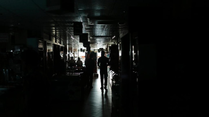 A Bangladeshi man walks in a shopping mall during a blackout in Dhaka, Bangladesh, Saturday, Nov. 1, 2014. Bangladesh was hit by a nationwide blackout on Saturday after a transmission line bringing electricity from neighboring India failed, but power was restored to many parts of the country within a few hours, an official said. (AP Photo/A.M. Ahad)