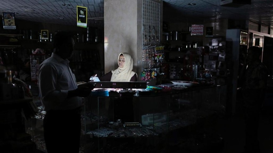 A Bangladeshi customer walks past a salesgirl in a shopping mall during a blackout in Dhaka, Bangladesh, Saturday, Nov. 1, 2014. Bangladesh was hit by a nationwide blackout on Saturday after a transmission line bringing electricity from neighboring India failed, but power was restored to many parts of the country within a few hours, an official said. (AP Photo/A.M. Ahad)
