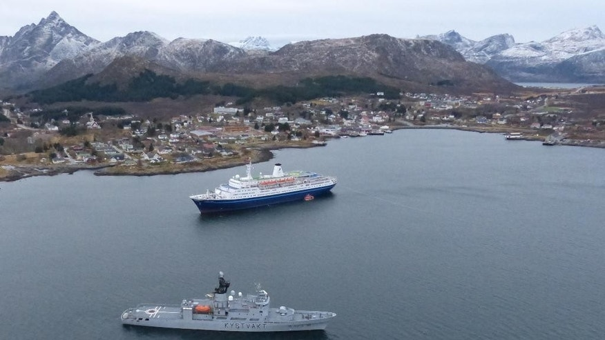 """This image made available by the Royal Norwegian Air Force taken from a rescue helicopter shows a Norwegian coast guard vessel in front of the  Bahamas-registered cruise liner """"Marco Polo"""" aground near Gravdal in northern Norway, Saturday Nov. 1, 2014. Passengers had been allowed to leave the cruise ship, which was carrying more than a thousand people when it ran aground in the Lofoten archipelago early Saturday. The same liner also ran aground briefly in a nearby archipelago in March, according to Norwegian media. The cause of that incident remained unclear. (AP Photo/Royal Norwegian Air Force) NORWAY OUT"""