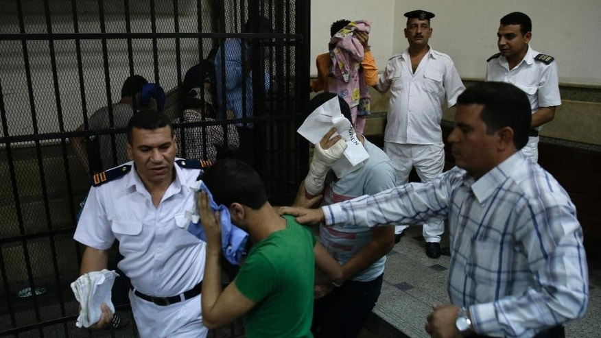 "Eight Egyptian men convicted for ""inciting debauchery"" following their appearance in a video of an alleged same-sex wedding party on a Nile boat cover their faces as they leave the defendant's cage in a courtroom in Cairo, Egypt, Saturday, Nov. 1, 2014. Saturday's verdict that sentenced each of them to three years in prison is the latest in a crackdown by authorities against gays, atheists, liberal and pro-democracy activists and violators of a draconian law on street protests. Consensual same-sex relations are not explicitly prohibited, but other laws have been used to imprison gay men in recent years. Egypt's crackdown is taking place as the country of nearly 90 million people appears to be steadily moving to the right, with jingoism and xenophobia dominating the media. (AP Photo/Hassan Ammar)"