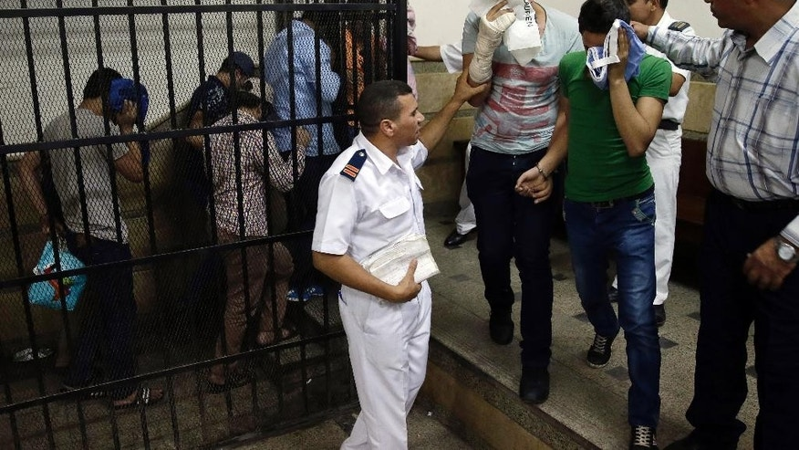 "Eight Egyptian men convicted for ""inciting debauchery"" following their appearance in a video of an alleged same-sex wedding party on a Nile boat leave the defendant's cage in a courtroom in Cairo, Egypt, Saturday, Nov. 1, 2014. Saturday's verdict that sentenced each of them to three years in prison is the latest in a crackdown by authorities against gays, atheists, liberal and pro-democracy activists and violators of a draconian law on street protests. Consensual same-sex relations are not explicitly prohibited, but other laws have been used to imprison gay men in recent years. Egypt's crackdown is taking place as the country of nearly 90 million people appears to be steadily moving to the right, with jingoism and xenophobia dominating the media. (AP Photo/Hassan Ammar)"