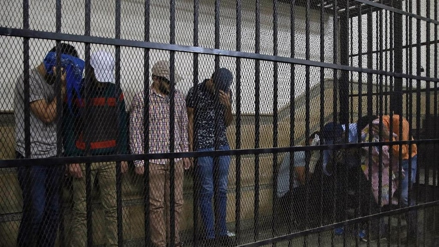 "Eight Egyptian men convicted for ""inciting debauchery"" following their appearance in a video of an alleged same-sex wedding party on a Nile boat appear in the defendant's cage in a courtroom in Cairo, Egypt, Saturday, Nov. 1, 2014. Saturday's verdict that sentenced each of them to three years in prison is the latest in a crackdown by authorities against gays, atheists, liberal and pro-democracy activists and violators of a draconian law on street protests. Consensual same-sex relations are not explicitly prohibited, but other laws have been used to imprison gay men in recent years. Egypt's crackdown is taking place as the country of nearly 90 million people appears to be steadily moving to the right, with jingoism and xenophobia dominating the media. (AP Photo/Hassan Ammar)"