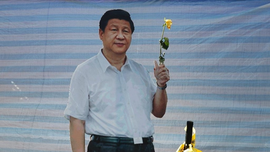 In this Wednesday, Oct. 29, 2014 photo, a flower is placed on a cut-out picture of Chinese President Xi Jinping by pro-democracy protesters in the occupied areas outside government headquarters in Hong Kong's Admiralty, Wednesday, Oct. 29, 2014. After more than a month in which scattered pro-democracy protests coalesced into an unprecedented social movement, that demand has gone unmet. Beijing has not budged an inch. (AP Photo/Kin Cheung)