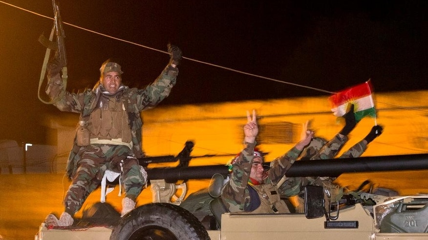 Iraqi Kurdish peshmerga fighters cheer as they leave the outskirts of Suruc, Turkey, towards the Turkey-Syria border, on the way to the Syrian city of Kobani,  Friday, Oct. 31, 2014. The 10 peshmerga fighters from Iraq who entered the embattled northern Syrian town of Kobani one day earlier returned to Turkey Friday to prepare for their forces' full deployment, and a senior Kurdish official blamed Ankara for the delay. (AP Photo/Vadim Ghirda)