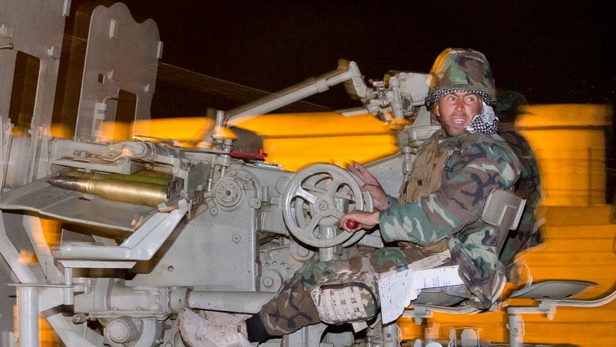 Oct. 31, 2014: An Iraqi Kurdish peshmerga fighter rides on an artillery weapon as he leaves the outskirts of Suruc, Turkey, towards the Turkey-Syria border, on the way to the Syrian city of Kobani