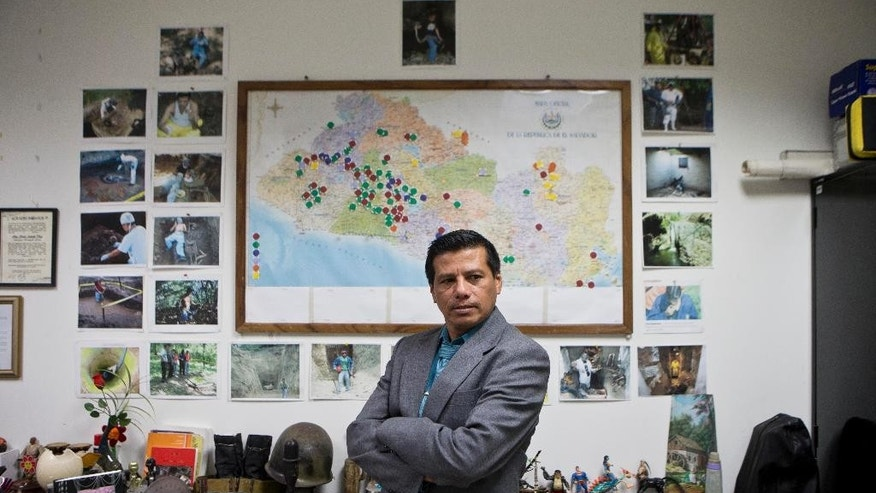 """In this Aug 20, 2014 photo, criminologist Israel Ticas poses for backdropped by a wall papered with images of his team members at work and a map of El Salvador marking points of reported violent cases, in San Salvador. Ticas calls himself the """"lawyer for the dead,""""  who sees the evidence of gang rape and sadistic methods of murder on a daily basis. (AP Photo/Esteban Felix)"""