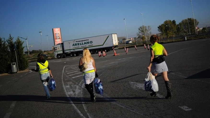 LLEIDA, SPAIN - OCTOBER 28:  Three prostitutes wear reflective vests as they walk along a road on October 28, 2010 near Els Alamus in Lleida, Spain. Prostitutes working near a highway roundabout near Els Alamus have this month started to wear the reflective jackets to avoid fines of 40 Euros following a police crackdown. (Photo by David Ramos/Getty Images)