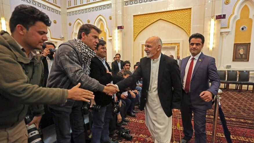 Afghanistan's President Ashraf Ghani Ahmadzai shakes hands with journalists before a press conference in Kabul, Afghanistan, Saturday, Nov. 1, 2014. Ghani Ahmadzai vowed that his crackdown on official corruption will ensure there is no repeat of a banking scandal in which almost $1 billion was embezzled, decimating confidence in the country's financial sector. (AP Photo/Rahmat Gul)