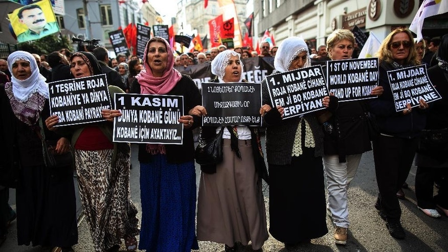 "Turkish Kurds march during a rally to support Syrian Kurds fighting Islamic State extremists in the embattled Syrian border town of Kobani or Ayn al-Arab, in Istanbul, Turkey, Saturday, Nov. 1, 2014. The placards read: "" Nov. 1, International Kobani Day."" (AP Photo/Emrah Gurel)"