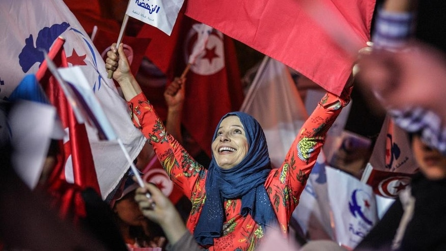 In this  Friday, Oct. 24, 2014, file photo a supporter of the moderate Islamist Ennahda Party waves party flags during a campaign rally in Tunis. Tunisians voted Sunday, Oct. 26. to elect a permanent parliament and complete a democratic transition that began when they overthrew their long-ruling dictator in 2011. (AP Photo/Aimen Zine, File)
