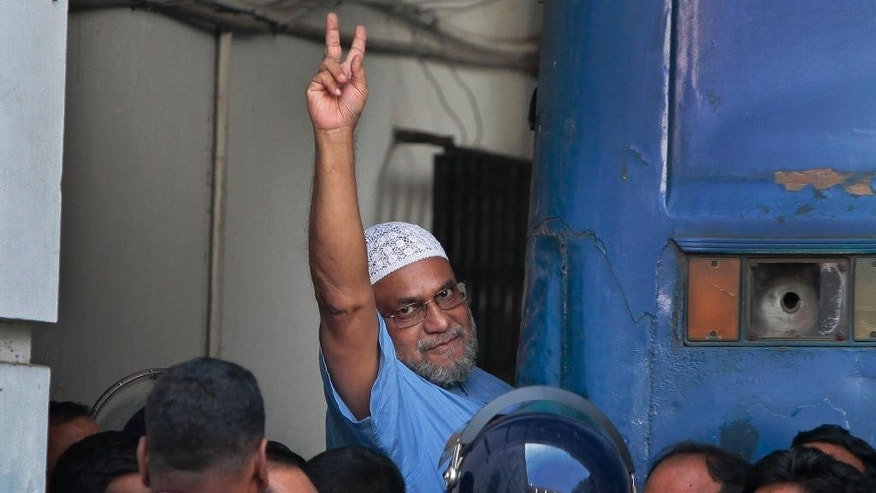 Mir Quashem Ali, a senior leader of the Bangladesh's largest Islamist party Jamaat-e-Islami shows victory sign as he enters a police van after a special tribunal sentenced him to death in Dhaka, Bangladesh, Sunday, Nov. 2, 2014. Ali is the second leader to be sentenced to death in a week for mass killings during the nation's 1971 independence war against Pakistan. (AP Photo/A.M. Ahad)