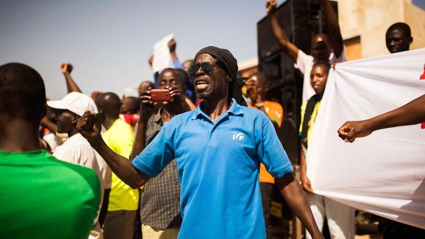 A man shouts out as he and others gather at the Place de Nation, as they ask for a civilian and democratic transition in Ouagadougou, Burkina Faso, Sunday, Nov. 2, 2014. Burkina Faso's new military leader is coming under growing pressure to hand over power to a civilian government. About 1,000 people gathered Sunday at the Place de Nation in Burkina Faso's capital. (AP Photo/Theo Renaut)