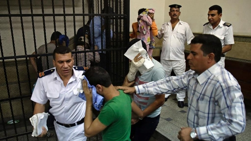 "Nov. 1, 2014: Eight Egyptian men convicted for ""inciting debauchery"" following their appearance in a video of an alleged same-sex wedding party on a Nile boat cover their faces as they leave the defendant's cage in a courtroom in Cairo, Egypt. (AP)"