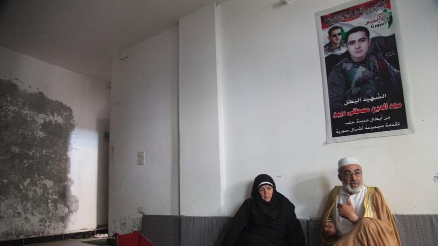 In this Tuesday, Oct. 28, 2014 photo, Mustafa Sobhi, 53, and his wife Faten Shaar, 52, sit under a portrait of their son Majed, who was killed while serving in the Syrian army, at a shelter in Tartous, Syria. The family was forced to flee the northern Syrian city of Aleppo to the coastal city of Tartous. Their story spotlights the pain and challenges as Syrians adjust to life in this truncated country, now in its fourth year of war, still firmly under the grip of President Bashar Assad, despite an armed rebellion to uproot him and losing territory to opposition rebels and the extremist Islamic State group. (AP Photo/Diaa Hadid)