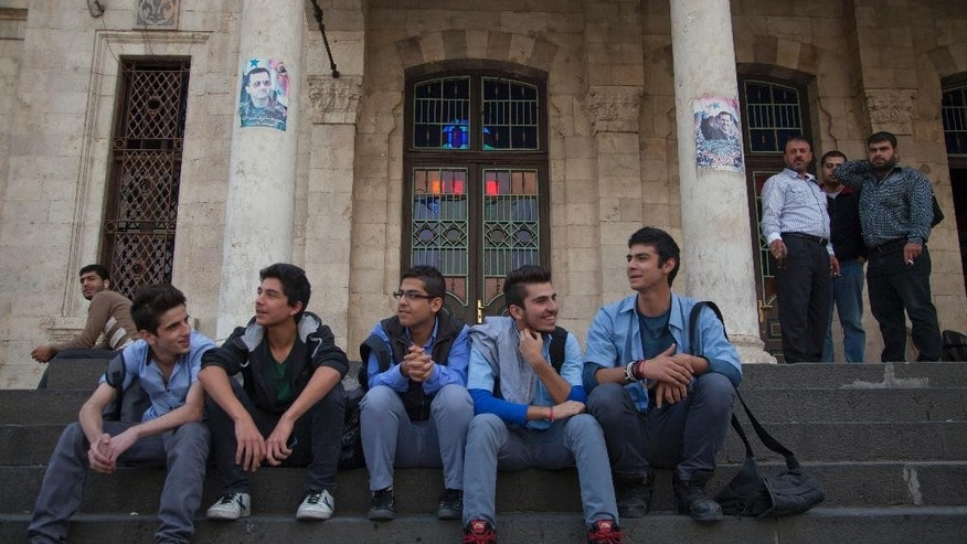In this photo taken Sunday, Oct. 26, 2014, young men sit on the stairs of the Ottoman-era Hijaz train station in the Syrian capital, Damascus. Despite being battered by a war, now in its fourth year, the country is still firmly under the grip of President Bashar Assad despite an armed rebellion to uproot him and losing territory to opposition rebels and the extremist Islamic State group. (AP Photo/Diaa Hadid)