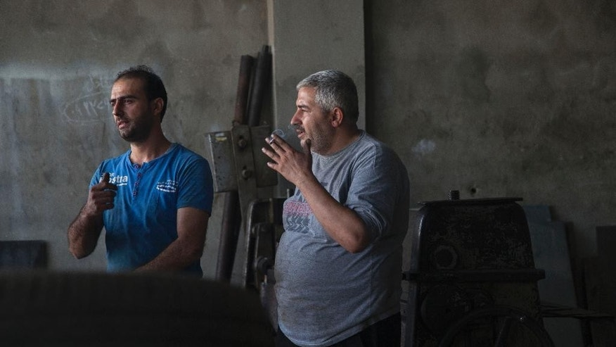 In this Tuesday, Oct. 28, 2014 photo, Mohammed Jallad, 32, left, speaks to another worker in an industrial workshop in the coastal Syrian city of Tartous. Jallad was forced to flee his home in the northern city of Aleppo after his home and business were destroyed in shelling.  With a loan, he reopened in Tartous. His story spotlights the pain and challenges as Syrians adjust to life in this truncated country, now in its fourth year of war, still firmly under the grip of President Bashar Assad, despite an armed rebellion to uproot him and losing territory to opposition rebels and the extremist Islamic State group. (AP Photo/Diaa Hadid)