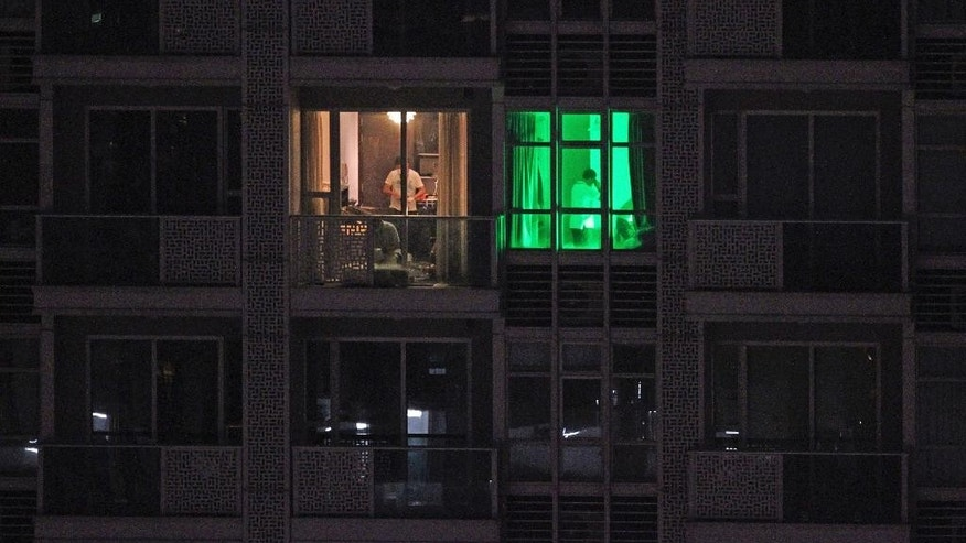 In this Saturday, Nov. 1, 2014 photo, police officers investigate inside the rooms of a foreign man's apartment in Hong Kong's Wan Chai nightlife and red light district. Hong Kong police arrested the foreign man suspected of killing two women, including one whose body was found inside a suitcase on the balcony of the apartment. Hong Kong news reports said the man was a British national. (AP Photo/Apple Daily) HONG KONG OUT, TAIWAN OUT