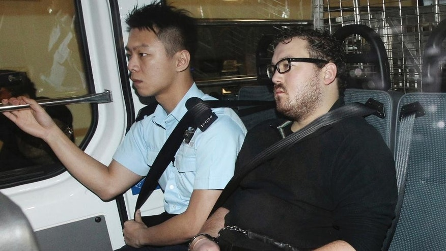 Rurik George Caton Jutting, right, is escorted by a police officer in an police van before appearing in a court in Hong Kong Monday, Nov. 3, 2014. Hong Kong police said Monday that they had charged the 29-year-old man with killing two women, including one whose body was found inside a suitcase on the balcony of the man's upscale apartment. (AP Photo/Apple Daily) HONG KONG OUT, TAIWAN OUT, NO ARCHIVE