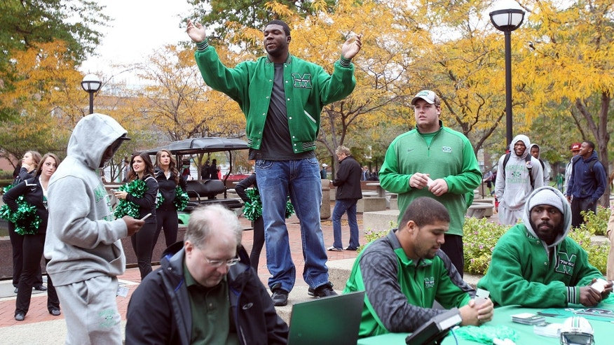 "Marshall college football player James Rouse, top center, announces free football game tickets to be given out as ESPN's ""All-Access"" visits the school's campus on Wednesday, Oct. 22, 2014, in Huntington, W.Va. (AP Photo/The Herald-Dispatch, Lori Wolfe)"