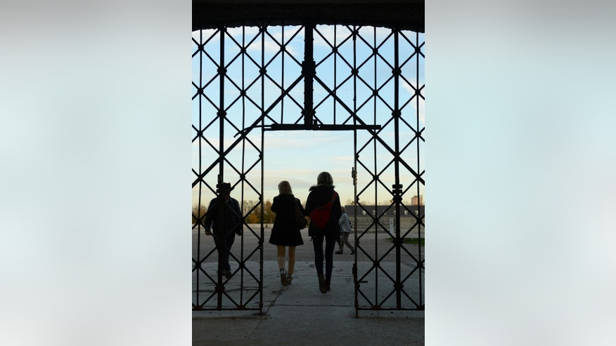 Two women walk through the main entrance of the concentration camp memorial in Dachau, Germany, Sunday, Nov. 2, 2014, where the wrought-iron gate  with the slogan 'Arbeit macht frei' ('work sets you free') is missing. Police said in a statement that security officials noticed early Sunday the gate section measuring 190 by 95 centimeters (75 by 37 inches) was missing. They said that whoever stole it during the night would have had to climb over another gate to reach it. (AP Photo/dpa, Andreas Gebert)