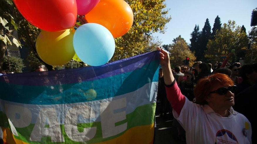 A gay rights activist holds up a rainbow flag during a gay pride march in Podgorica, Montenegro, Sunday, Nov. 2, 2014. Protected by hundreds of riot police, about two hundred gay activists marched peacefully in Montenegro, a staunchly conservative Balkan country seeking EU membership.(AP Photo/Darko Vojinovic)