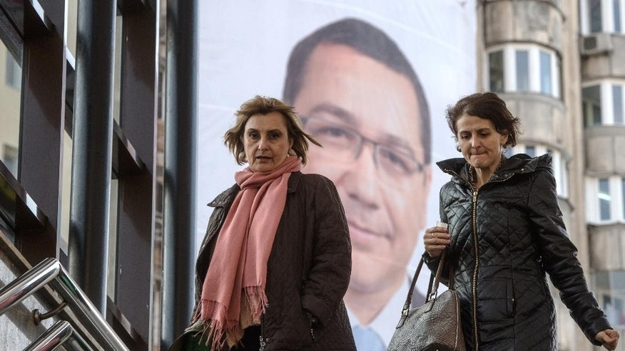 Two women walk down a flight of stairs in Bucharest, Romania, Friday, Oct. 31, 2014, backdropped by a campaign poster, attached to the facade of an apartment block, depicting Prime Minister Victor Ponta, leader of the ruling Social Democracy Party (PSD) who runs for president in elections set to take place on Nov. 2. Romanians go to the polls on Sunday to elect a new leader as President Traian Basescu steps down after 10 years. (AP Photo/Andreea Alexandru, Mediafax) ROMANIA OUT
